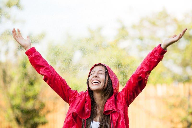 Femme joyeux jouant sous la pluie images libres de droits
