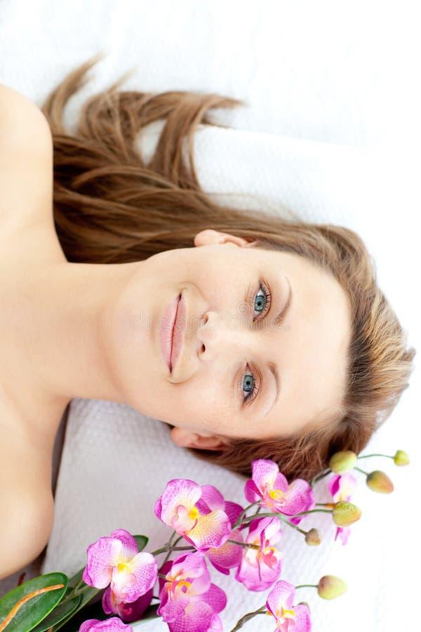 Femme joyeux se trouvant sur une table de massage avec la fleur images stock