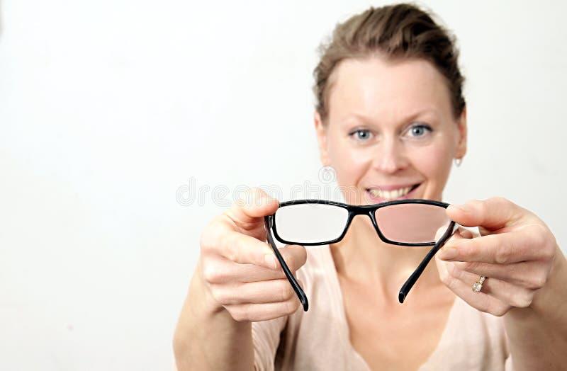 Femme jugeant des verres de lecture prêts à être employé image stock