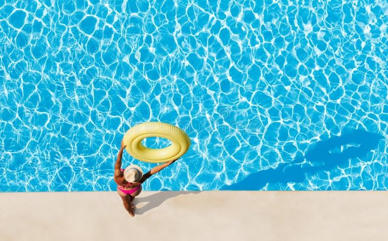 Femme jugeant l'anneau en caoutchouc aérien au poolside photographie stock