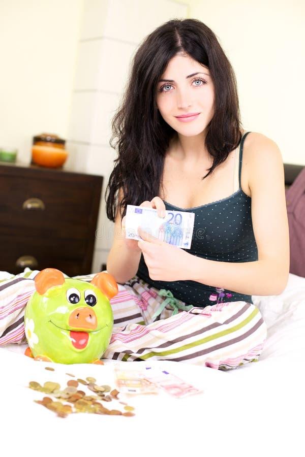 Femme jugeant l'argent avec la tirelire heureux photo stock