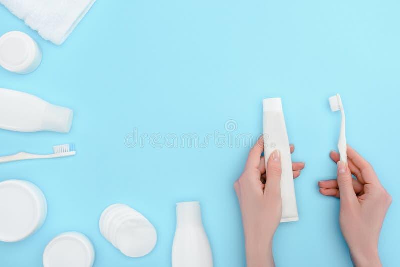 Femme jugeant la brosse à dents et la pâte dentifrice d'isolement sur le bleu avec les bouteilles cosmétiques de crème et de loti photo stock
