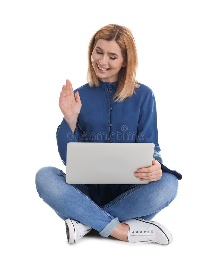 Femme ? l'aide de l'ordinateur portable pour la causerie visuelle d'isolement sur le blanc photo stock