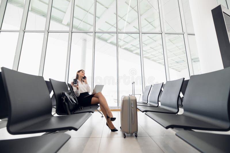 Femme ? l'aide de l'ordinateur portable sur le terminal d'a?roport se reposant avec la valise de bagage pour le vol de attente de photographie stock