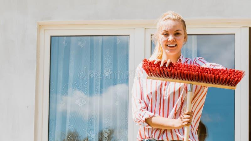 Femme ? l'aide du balai pour nettoyer le patio d'arri?re-cour images stock