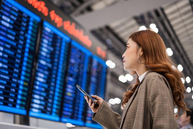 Femme ? l'aide du smartphone avec le conseil de l'information de vol ? l'a?roport image libre de droits
