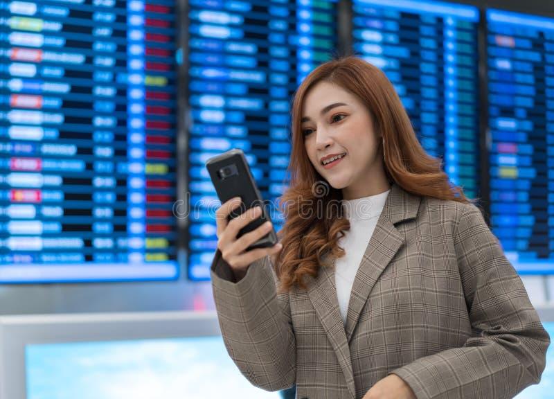 Femme ? l'aide du smartphone avec le conseil de l'information de vol ? l'a?roport photo stock