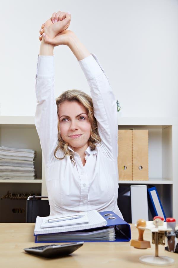Femme l'exerçant en arrière dans le bureau photos libres de droits