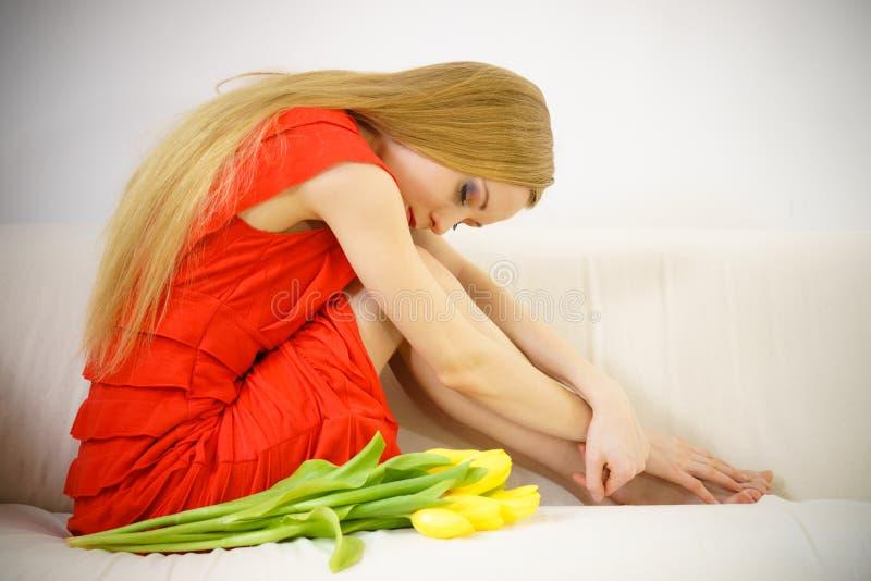 Femme ?l?gante triste s'asseyant sur le sofa avec la tulipe photographie stock libre de droits