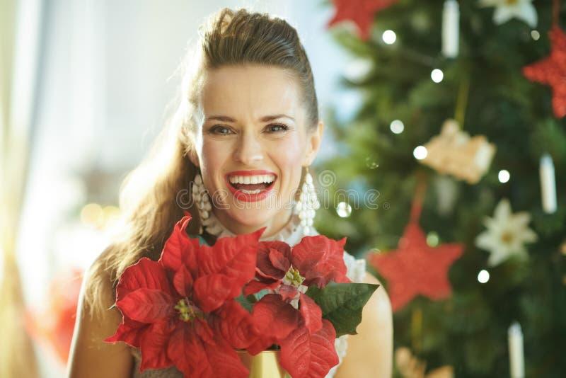 Femme ? la mode de sourire avec la poinsettia rouge pr?s de l'arbre de No?l images stock