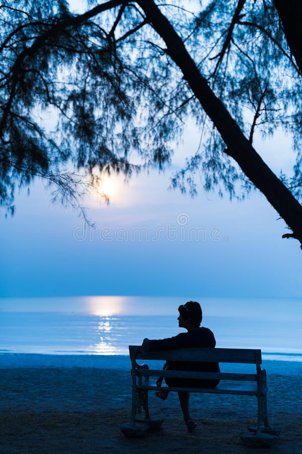 Femme la nuit avec la lune sur la plage image stock