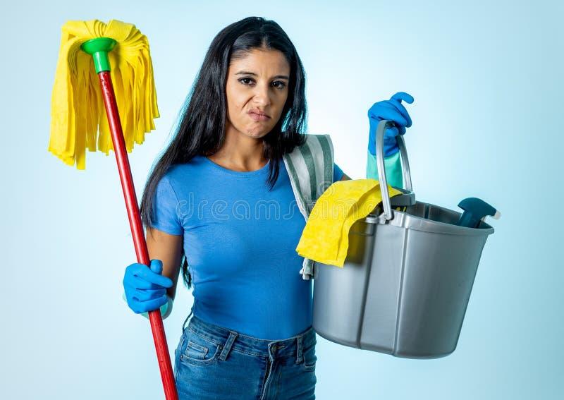 Femme latine attirante ennuyée et agitée du nettoyage et de la maison kipping photo stock