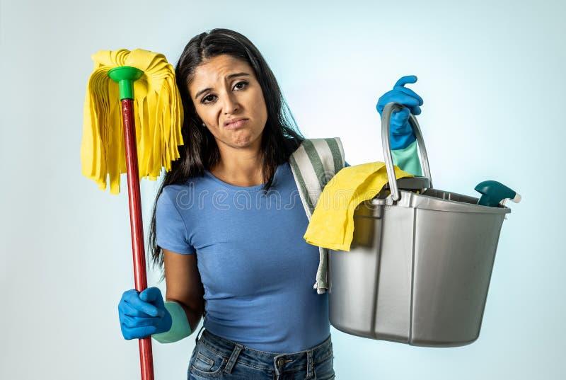 Femme latine attirante ennuyée et agitée du nettoyage et de la maison kipping photographie stock libre de droits