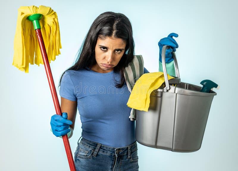 Femme latine attirante ennuyée et agitée du nettoyage et de la maison kipping image stock
