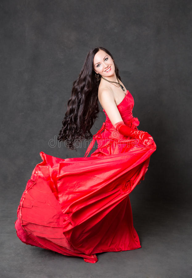 Femme latine avec de longs cheveux dans la danse de ondulation rouge de robe dans l'action avec le tissu de vol photos libres de droits