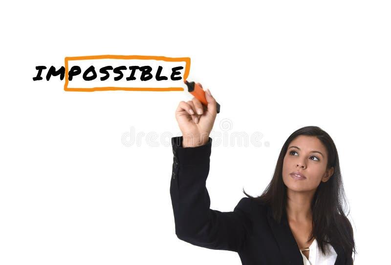 Femme latine dans l'écriture de costume de bureau avec le marqueur sur l'écran ou conseil tournant impossible dans possible images stock