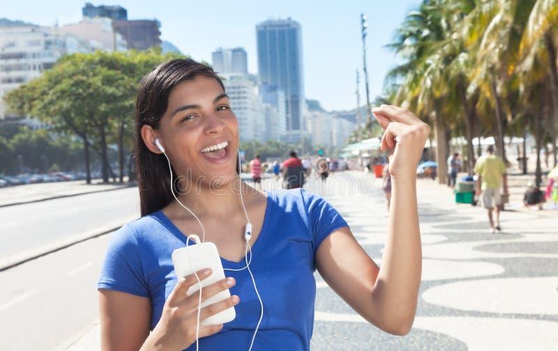 Femme latine de danse écoutant la musique avec le téléphone images stock