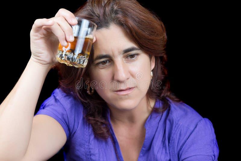 Femme latine ivre et triste tenant un verre de boisson alcoolisée image stock