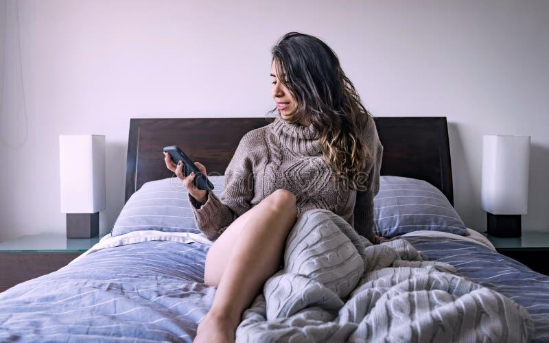 Femme latine observant le téléphone portable dans sa chambre à coucher, huitième photo photographie stock