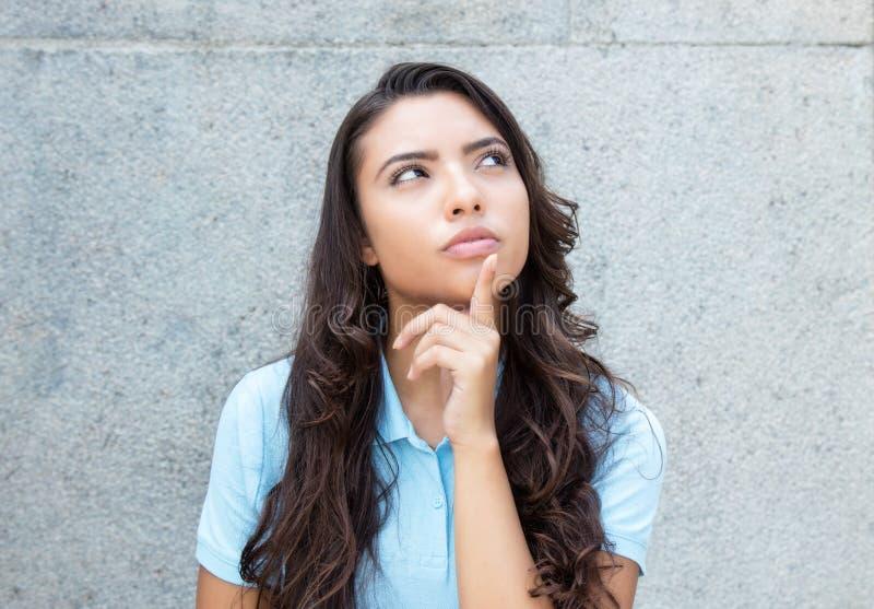 Femme latino-américaine de pensée avec de longs cheveux extérieurs dans le résumé photo stock
