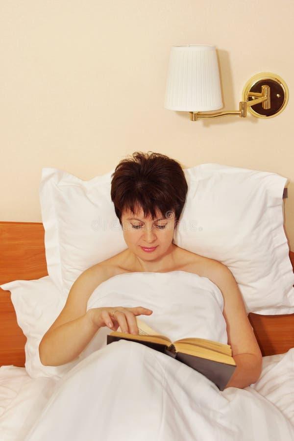 Femme lisant le livre avant le sommeil photos stock