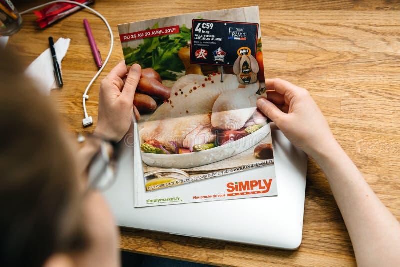 Femme lisant simplement le bulletin d'information de journal de brochure d'Auchan images stock