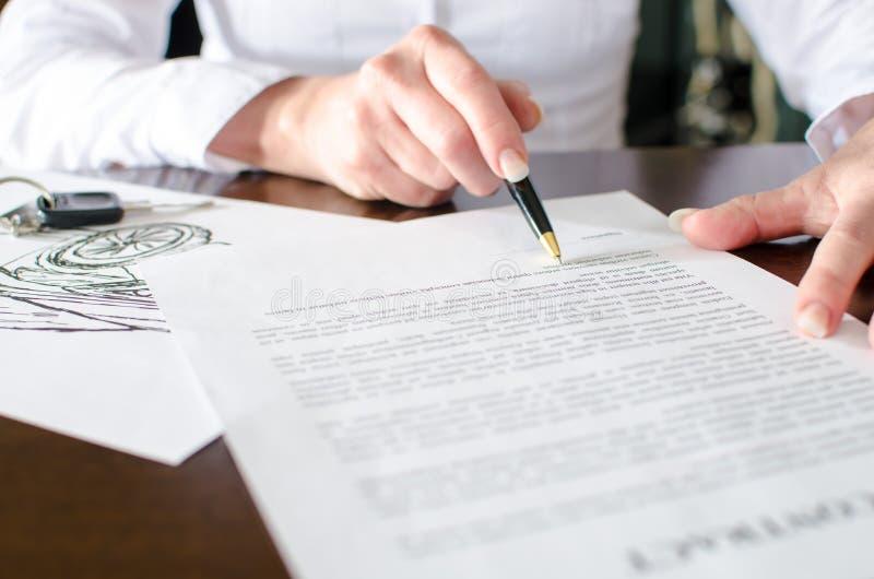 Femme lisant un contrat d'achat de voiture images stock