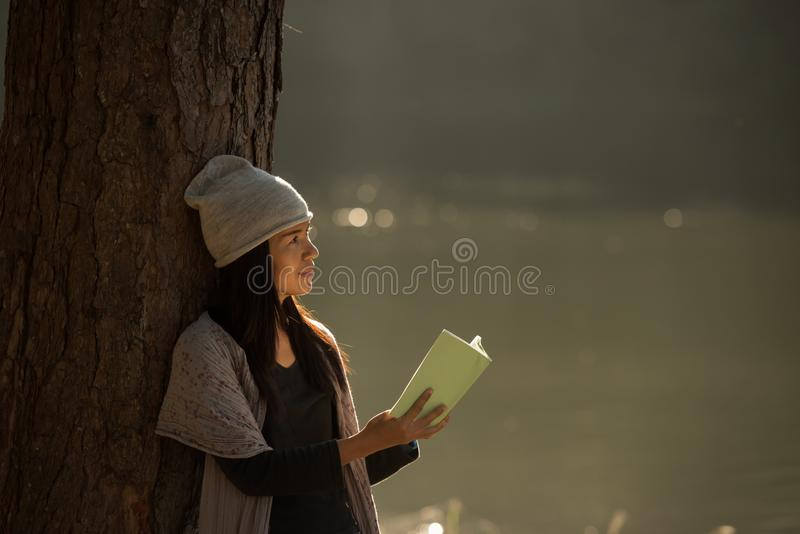 Femme lisant un livre dans la nature image stock