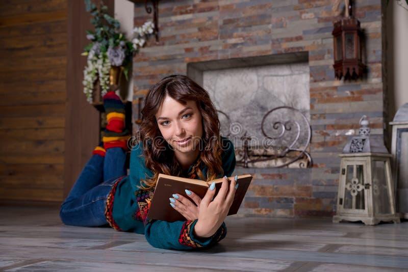 Femme lisant un livre et appréciant un chocolat chaud par la cheminée Mensonge sur l'étage plancher de chauffage, chauffage par l image libre de droits