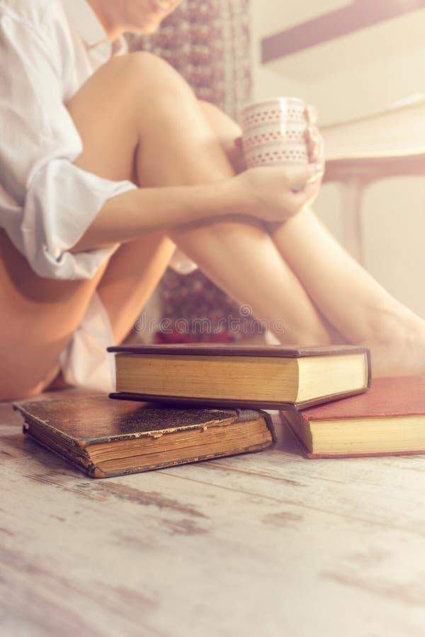 Femme lisant un livre et buvant du café dans sa maison confortable photo libre de droits