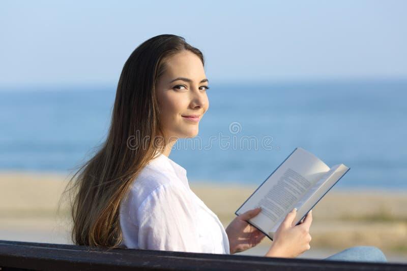 Femme lisant un livre et regardant l'appareil-photo photo libre de droits