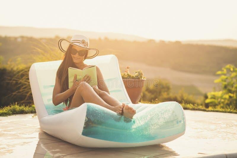 Femme lisant un livre par la piscine photographie stock libre de droits