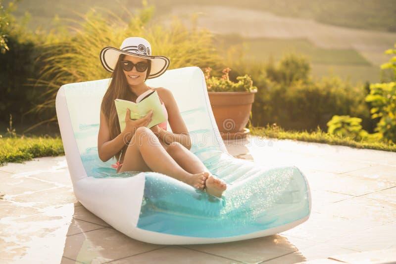 Femme lisant un livre par la piscine photos libres de droits