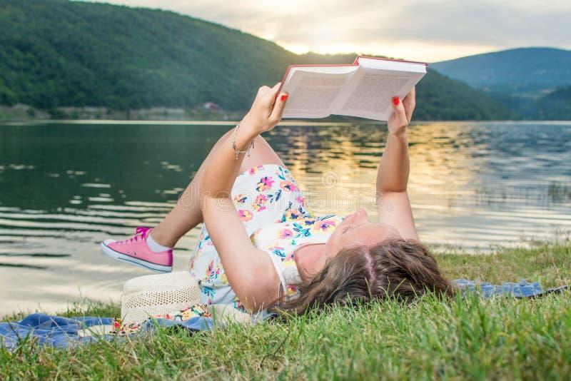Femme lisant un livre par le lac Relaxation soloe images libres de droits