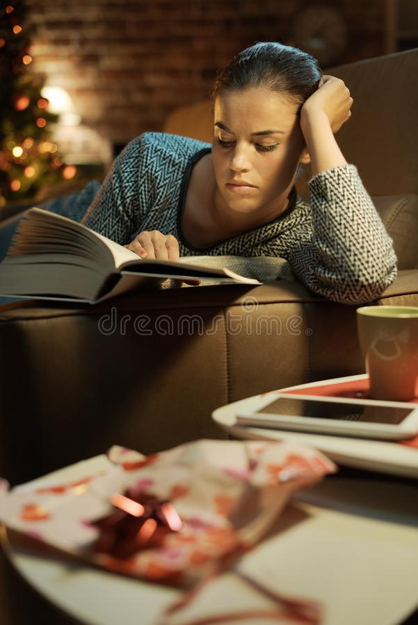 Femme lisant un livre qu'elle a re?u comme cadeau photo libre de droits
