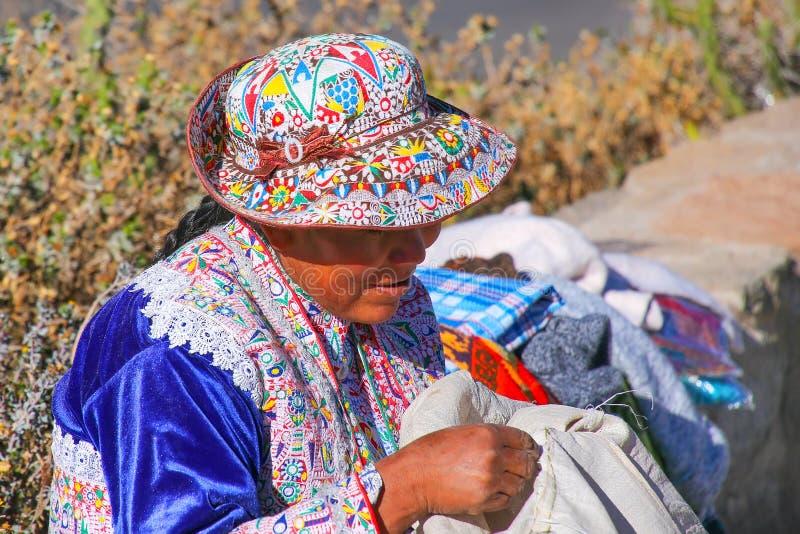 Femme locale s'asseyant chez Mirador Cruz del Condor en canyon de Colca, image libre de droits