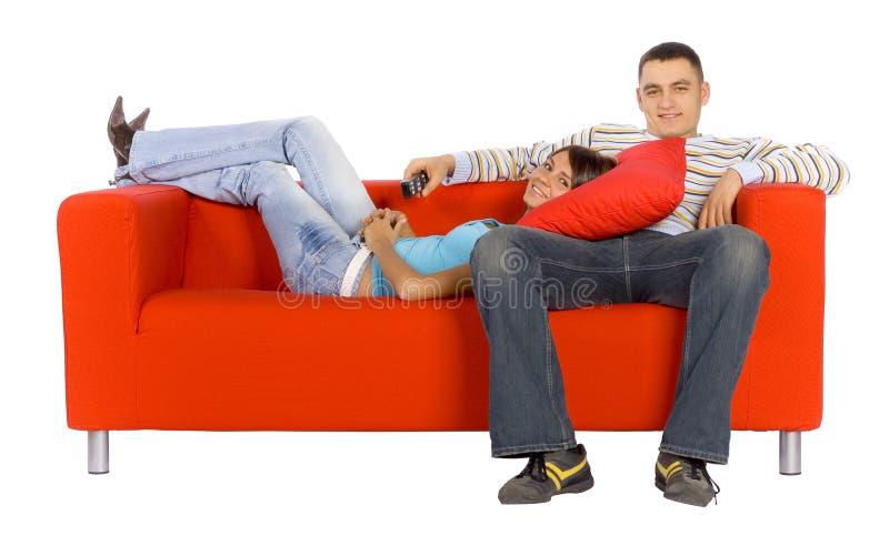 femme lointain orange d'homme confortable de divan photographie stock libre de droits