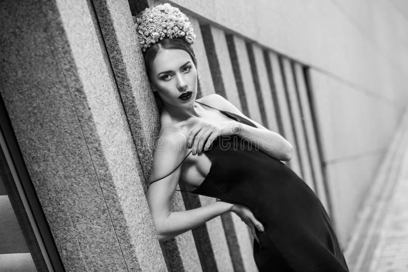 Femme luxueuse dans la couronne florale et la robe noire posant tandis que prairie images libres de droits