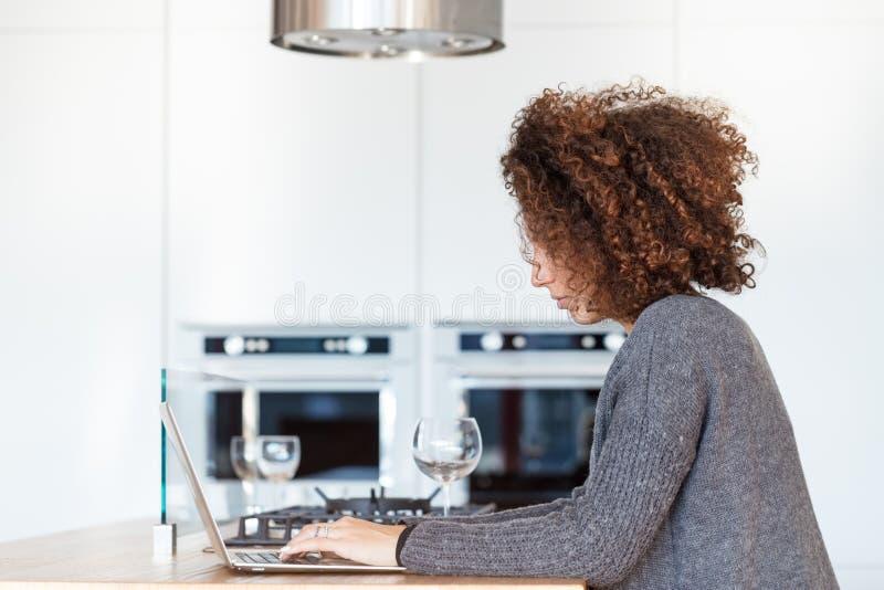 Femme méconnaissable avec l'ordinateur portable dans la cuisine photos libres de droits
