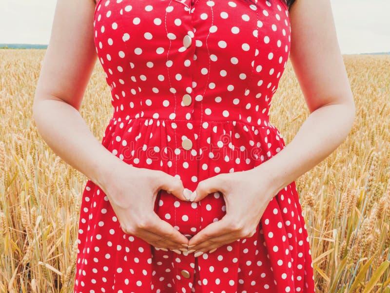 Femme méconnaissable enceinte la position rouge de robe de point de polka dans le domaine de blé et en montrant le symbole de coe photographie stock libre de droits