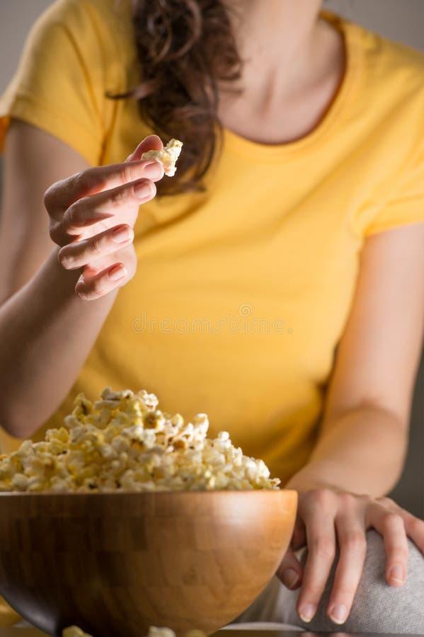 Femme méconnaissable mangeant du maïs éclaté image libre de droits