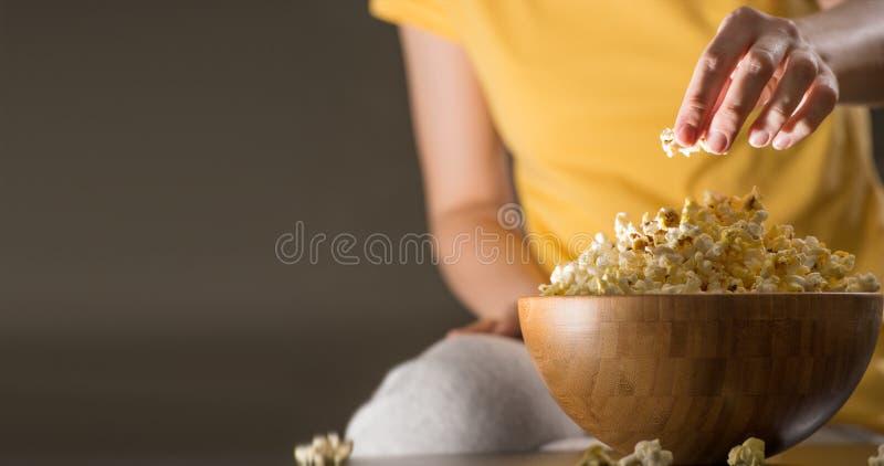 Femme méconnaissable mangeant du maïs éclaté images libres de droits