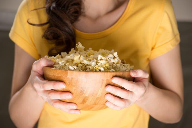 Femme méconnaissable mangeant du maïs éclaté photo libre de droits