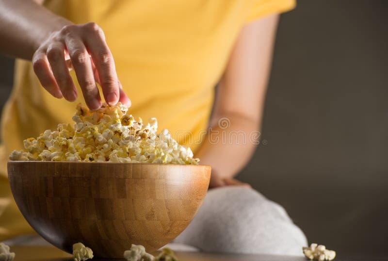 Femme méconnaissable mangeant du maïs éclaté au cinéma image libre de droits