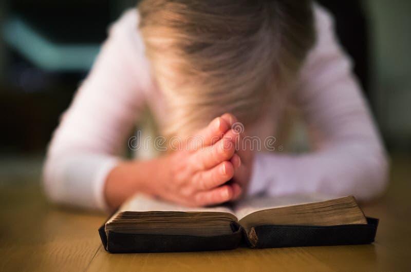 Femme méconnaissable priant, mains étreintes ensemble sur son Bibl photographie stock