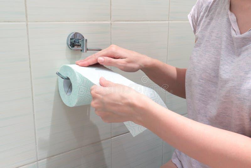 Femme méconnaissable, se reposant sur une toilette et un rebobinage et arracher un papier hygiénique Image de concept des problèm photographie stock libre de droits