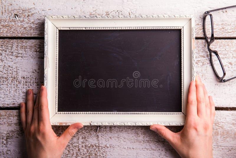 Femme méconnaissable tenant le cadre de tableau vide, lunettes St photographie stock libre de droits