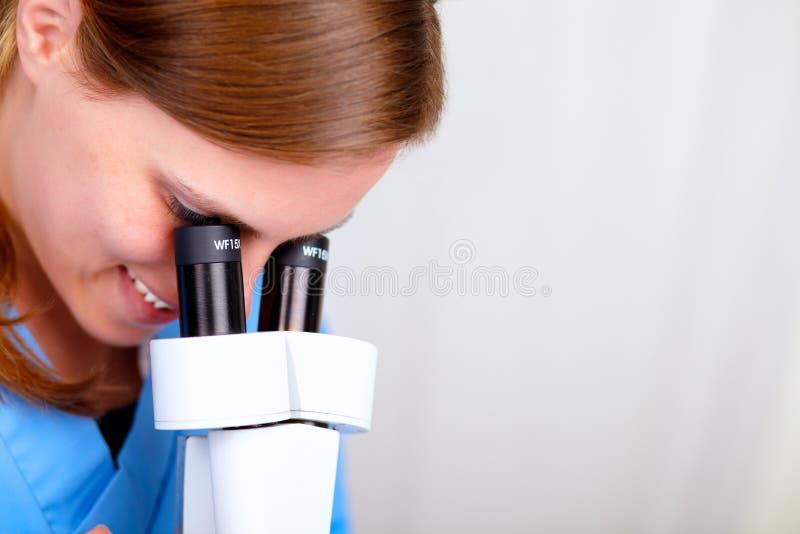 Femme médical professionnel à l'aide d'un microscope images stock