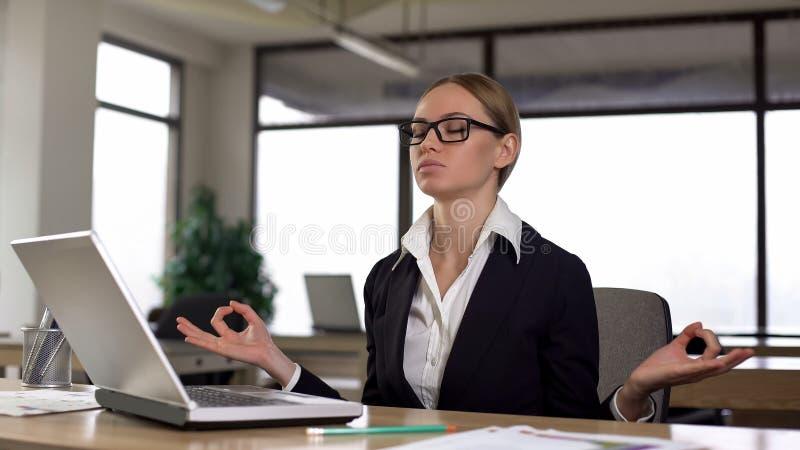 Femme méditant au bureau, réduisant des contraintes du travail et l'irritation, détendant photo stock