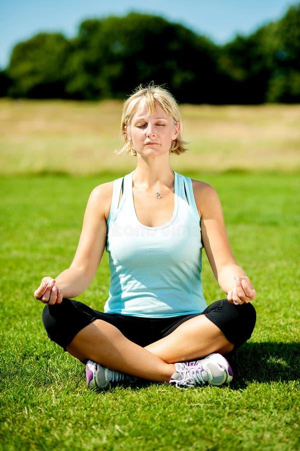 Femme méditant dehors un jour ensoleillé images stock